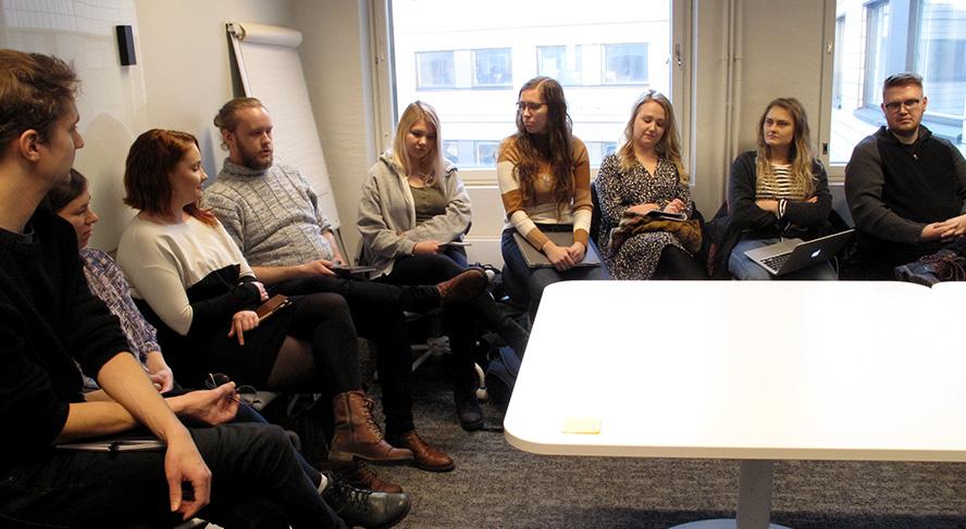 Ihmisiä kokoushuoneessa pöydän ympärillä.