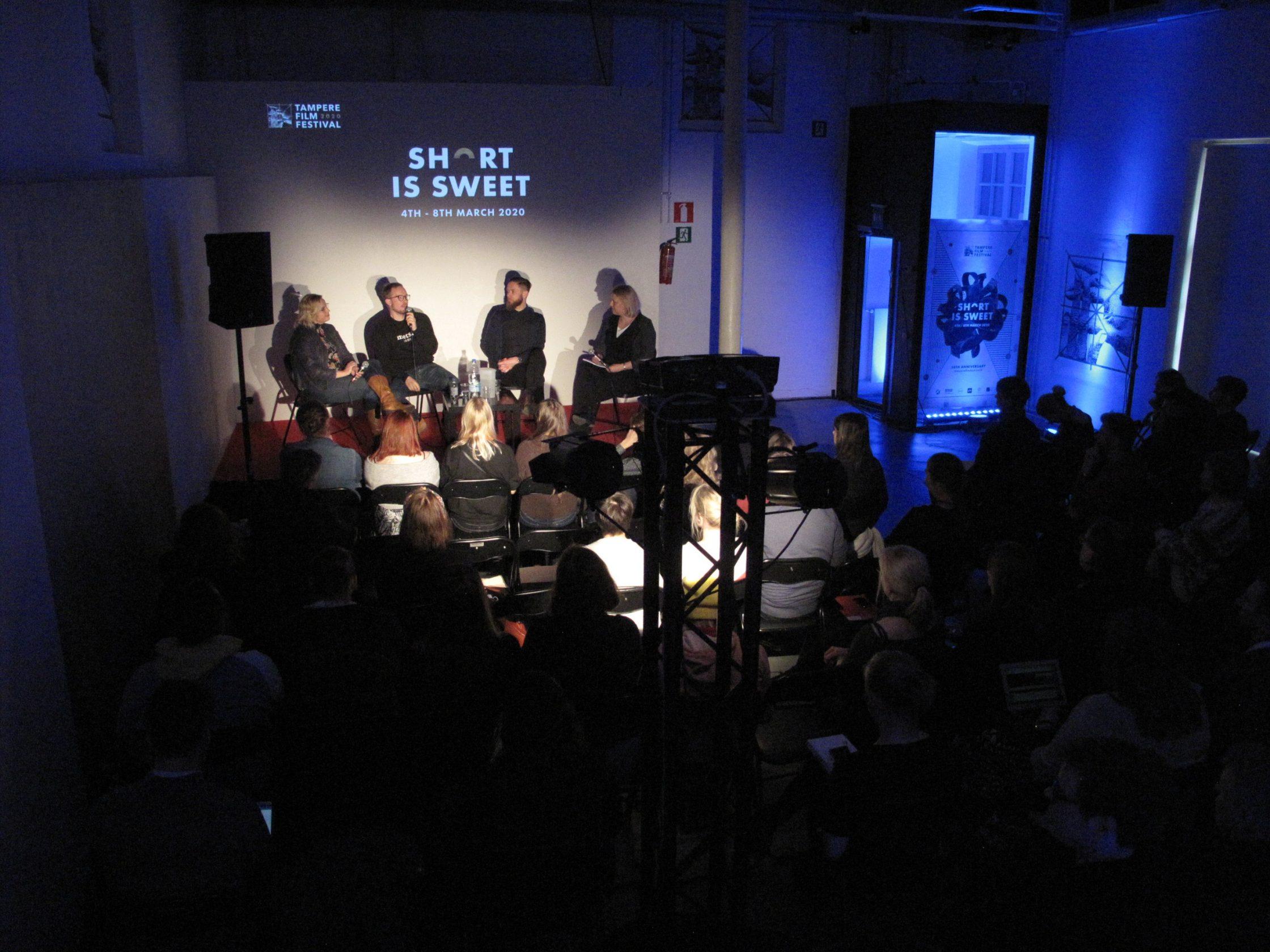 Seminaaritila, käynnissä paneelikeskustelu, lavalla neljä keskustelijaa, paljon yleisöä.