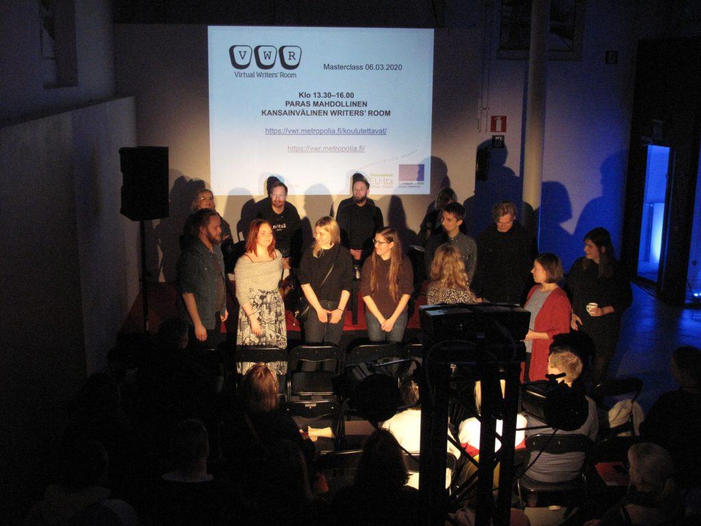 Seminaaritila, lavan edessä yhdeksän koulutettavaa esittäytymässä yleisölle.