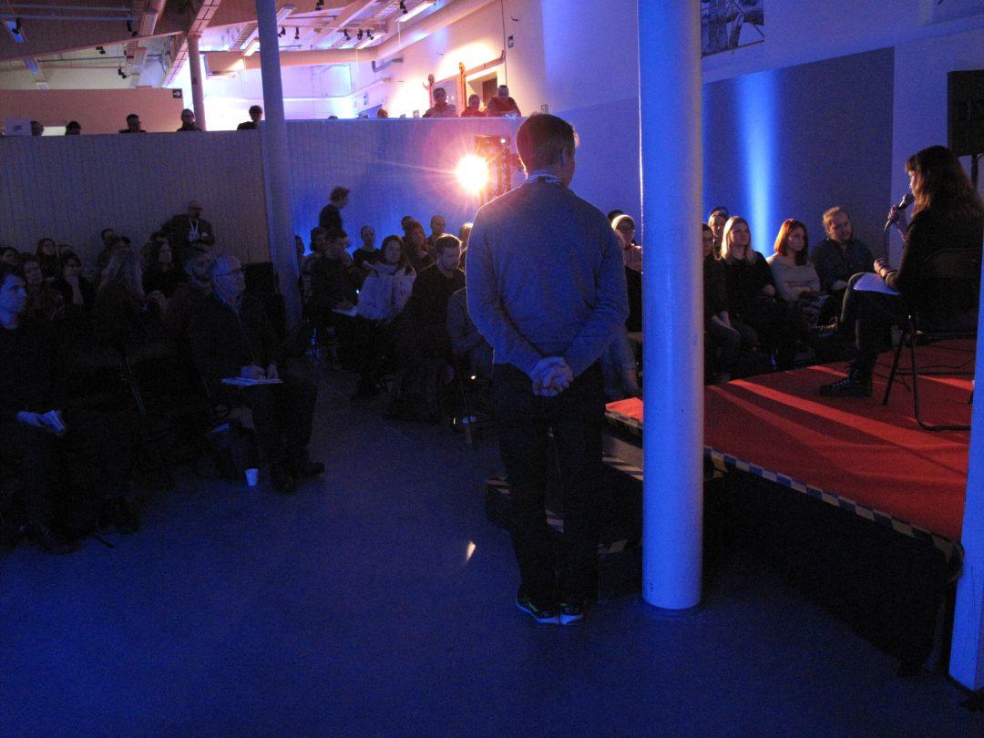Seminaaritila lavan takaa, runsaasti yleisöä näkyvissä.
